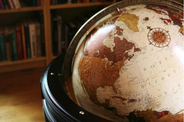 Zu sehen ist ein alter Globus vor einem Buchregal