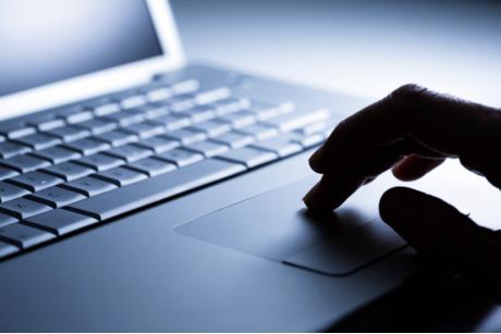 Zu sehen sind Finger über eine Laptop-Tastatur