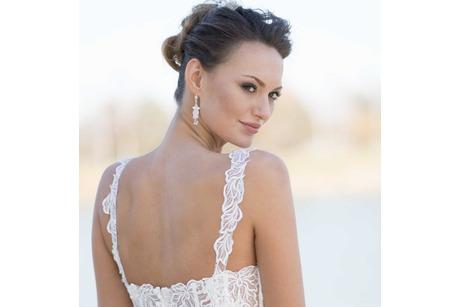 Braut schaut über Schulter mit Brautschmuck