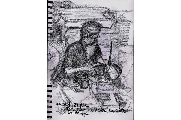 un artisan soude une théière en cuivre