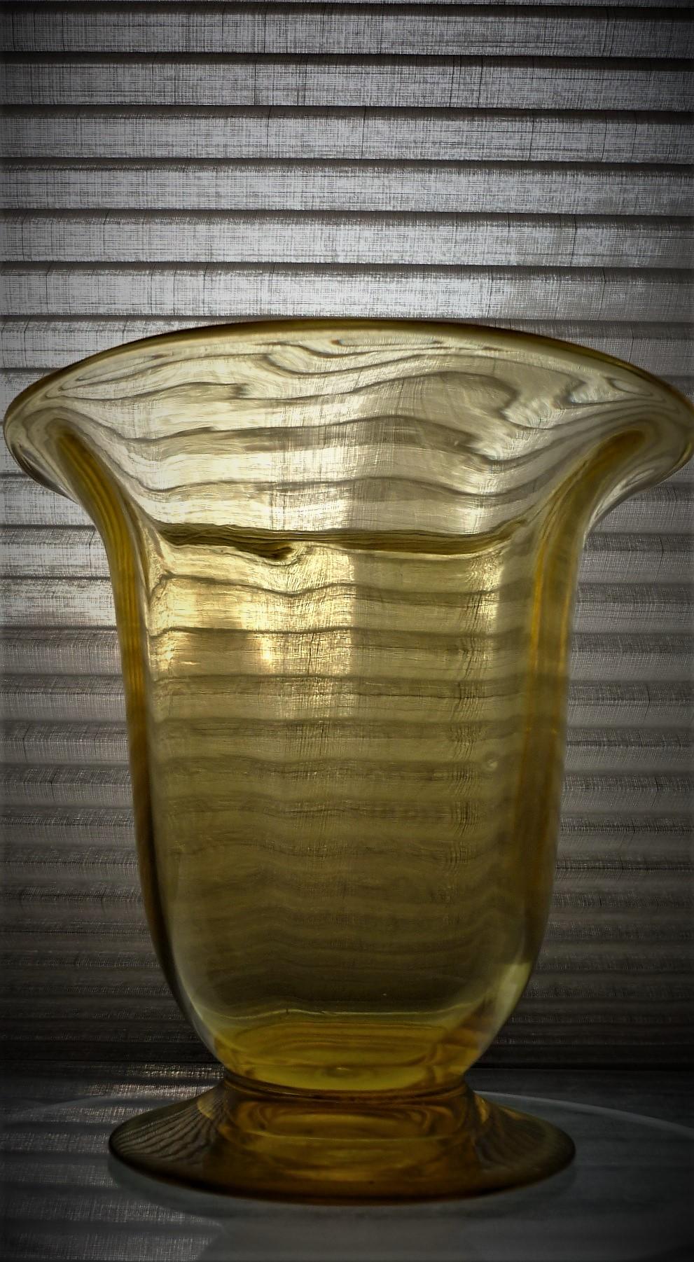 Webb Crystal flared rim pedestal vase in a light amber glass.