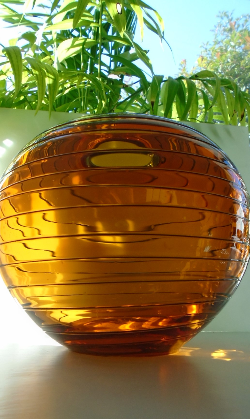 Vintage Murano style large globular glass bowl with a narrow opening.Formed from a clear honey coloured amber glass with a fine trailed horizontal decoration.