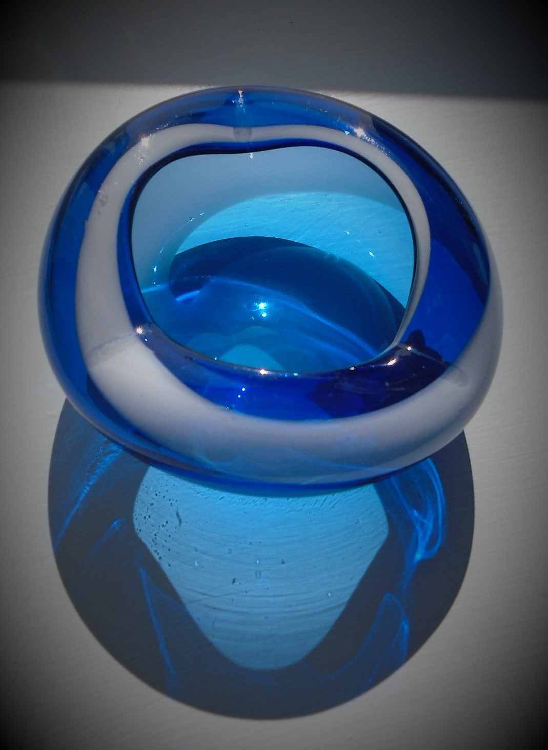 Offered for sale is a pretty vintage blue glass Murano bowl with a white glass stripe decoration