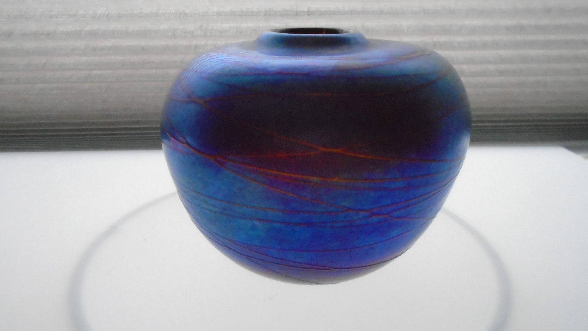 Stunning example of English Glass maker Siddy Langley's work in the form of a 1975 vintage blue iridescent narrow necked vase.