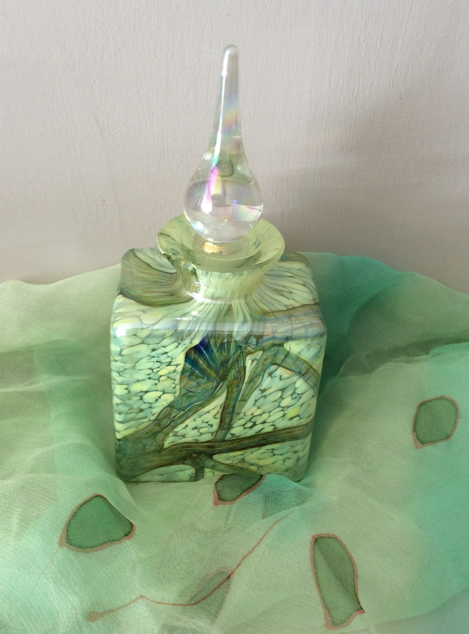 Iridescent Glass Perfume Bottle with abstract decoration over yellow and green