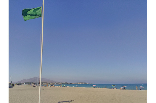 sandy_beach_blue_skies_and_green_flag_atop_pole