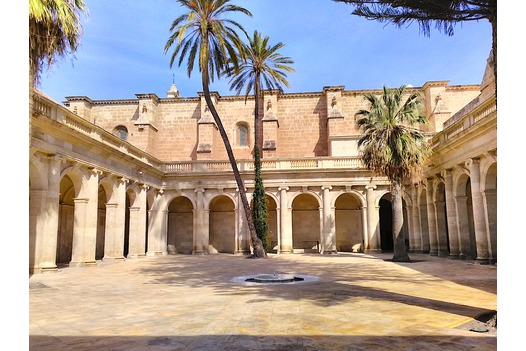 ancient_courtyard_with_stone_arches_and_palm_trees