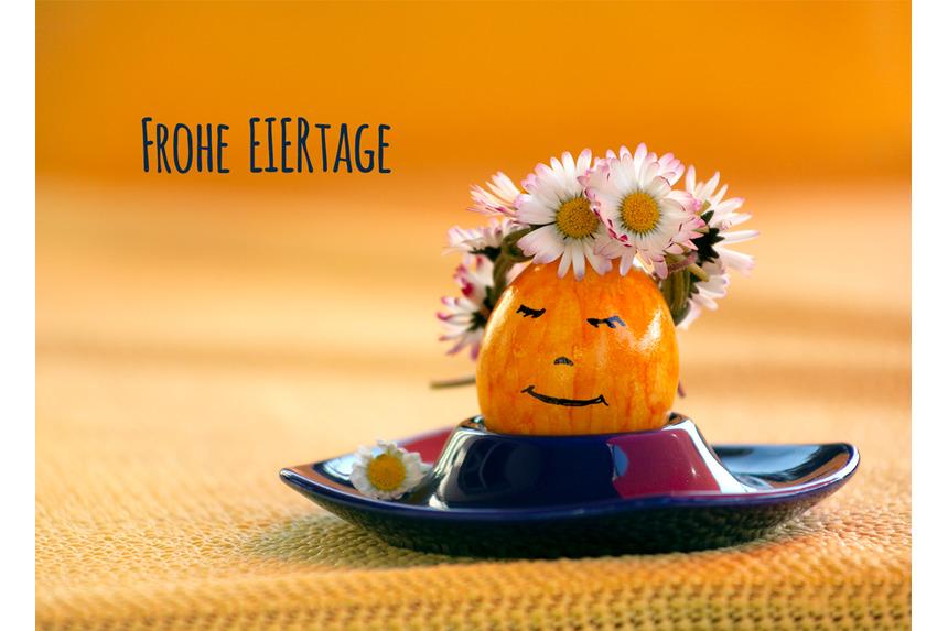 gelbes Osterei mit fröhlichem Gesicht und Blümchen