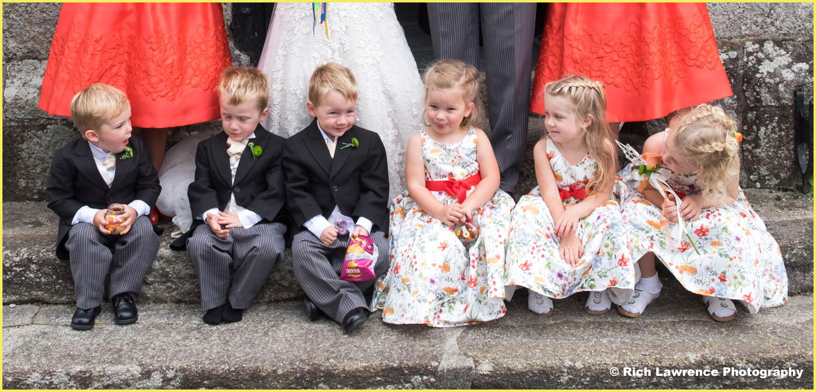 Bridesmaids and page boys sitting on church steps