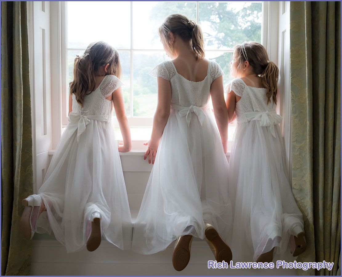 Three bridesmaids looking through window
