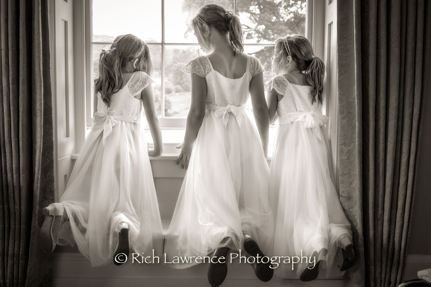 Three bridesmaids looking out of a window
