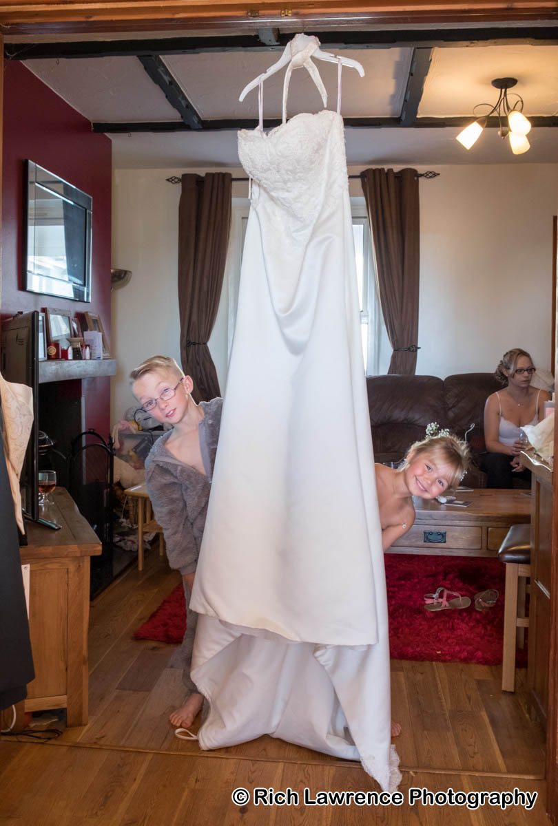 Children looking out from behind wedding dress