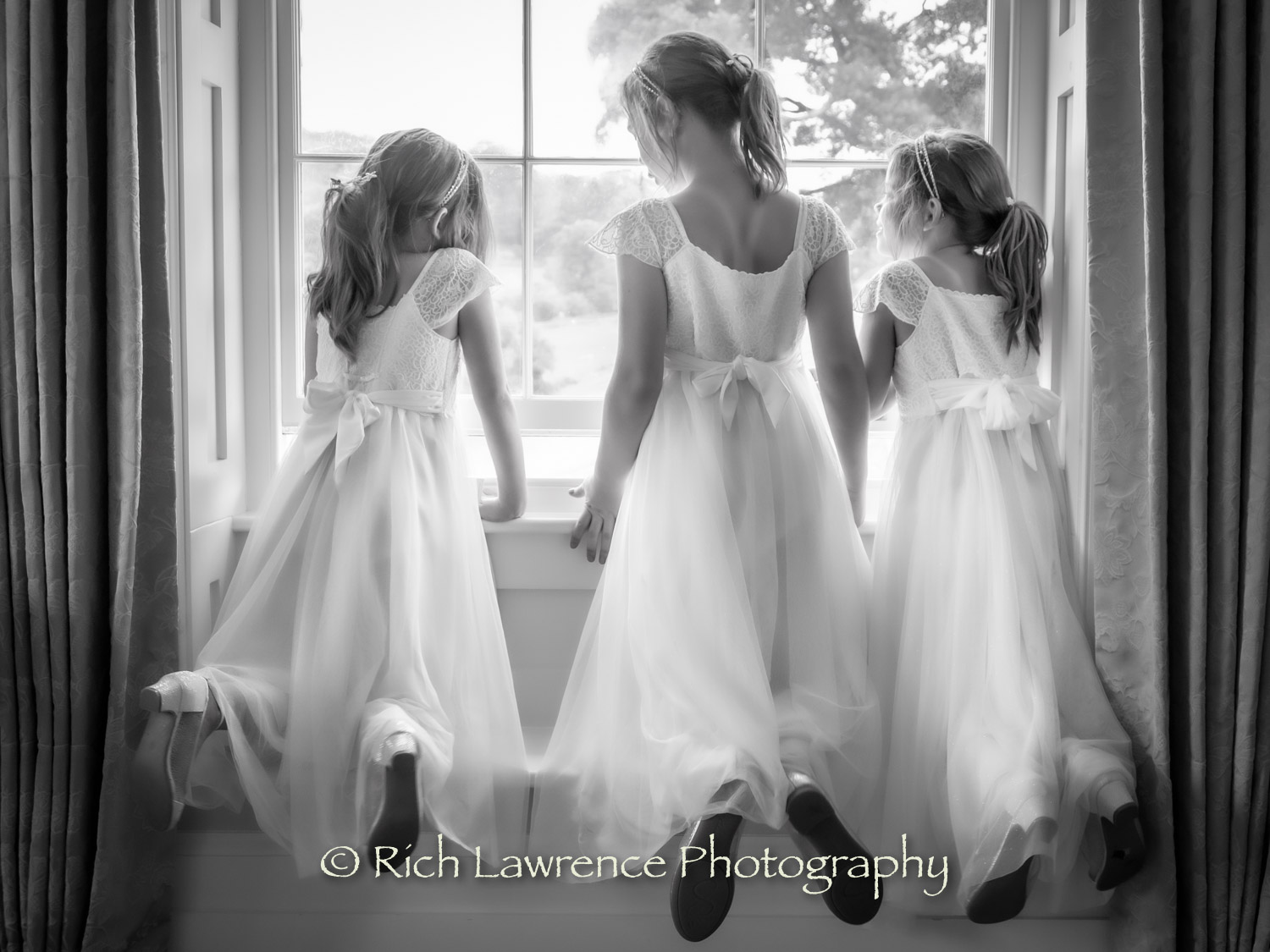 Three bridesmaids looking out of a window.