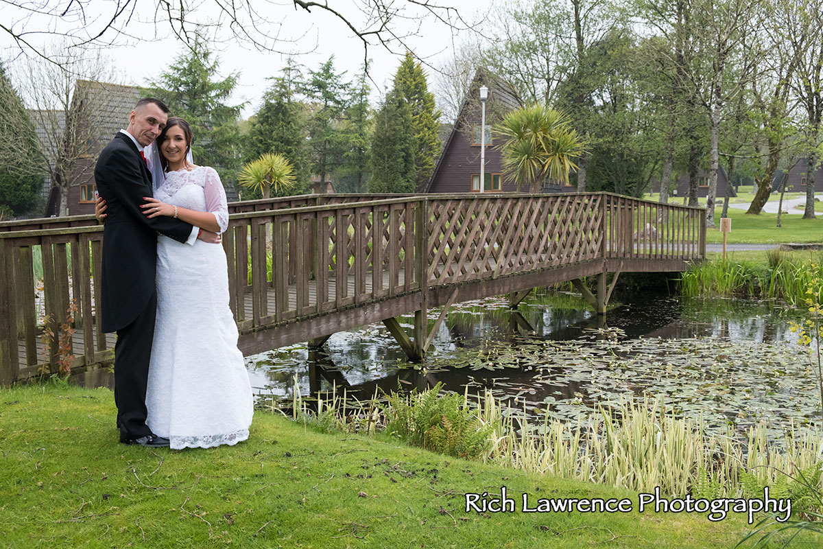 Bride and groom standing by a bridge near water
