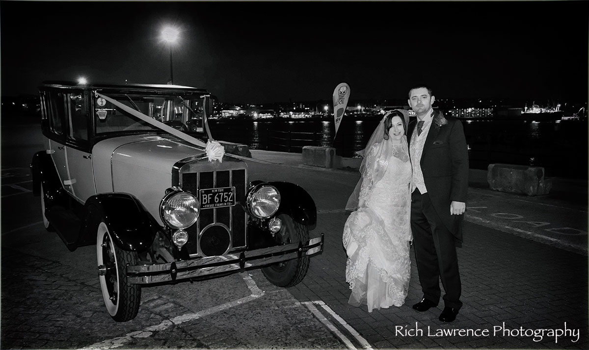 Bride and groom pose by wedding car
